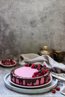 Torta mousse di ribes decorata con pezzi di biscotti oreo e lamponi.