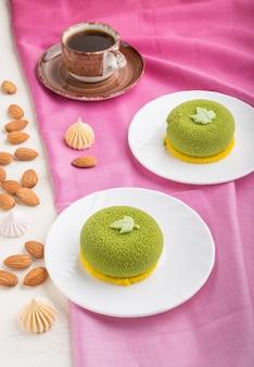 Torta mousse verde con crema al pistacchio e una tazza di caffè. vista laterale