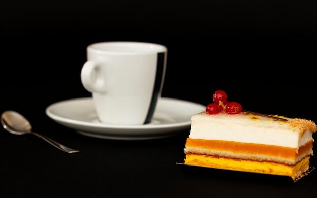 Torta multistrato con ariosa crema bianca e ribes rosso, dessert da far venire l'acquolina in bocca, tazza bianca con un cucchiaino