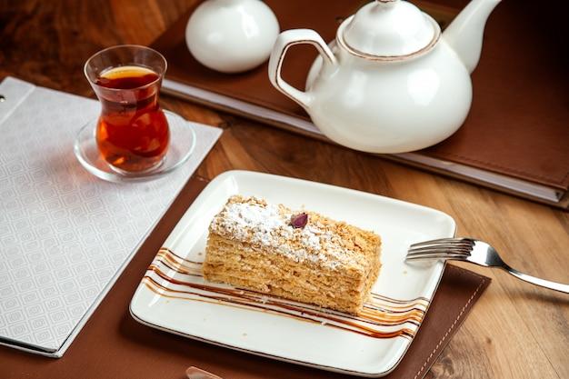 Torta napoleone con crema di burro e zucchero in polvere e tè scuro sul tavolo
