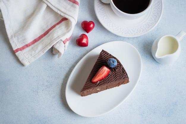 Torta natalizia per dessert. pezzo di dolce di cioccolato delizioso con la tazza di caffè e latte sulla tavola del calcestruzzo della pietra blu. concetto di cibo per la colazione. decorazione festiva