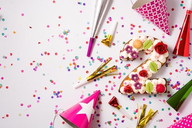 Torta numero due decorata con fiori, macarons e coriandoli isolati su superficie bianca copia spazio