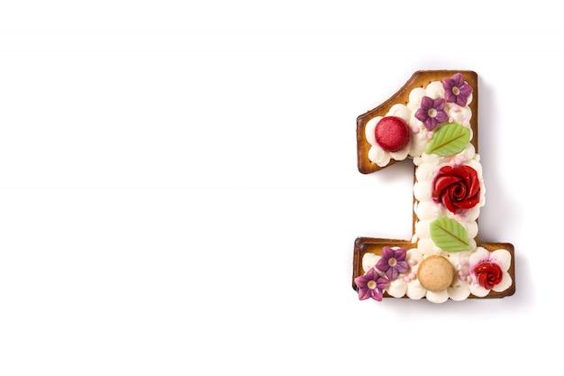 Torta numero uno decorata con fiori e macarons su bianco.
