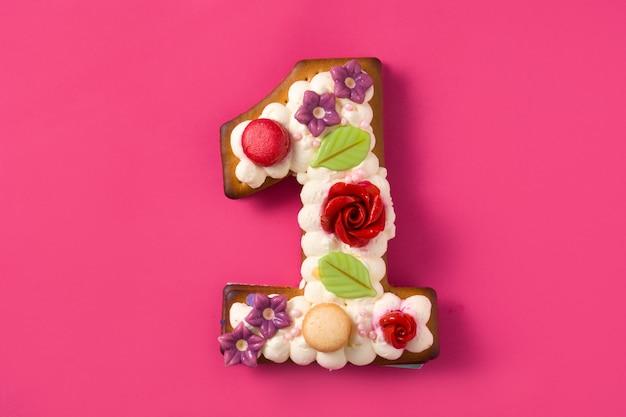 Torta numero uno decorato con fiori e biscotti sulla superficie rosa.