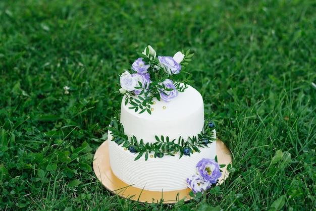 Torta nunziale bianca con fiori lilla e rametti di verde con fiori