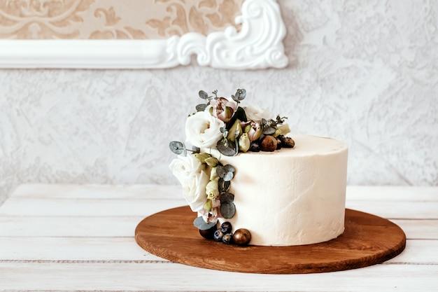 Torta nunziale bianca decorata con fiori di eustoma ed eucalipto. posto per il testo.