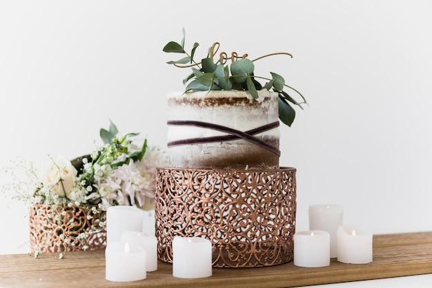 Torta nunziale deliziosa con testo di amore contro fondo bianco