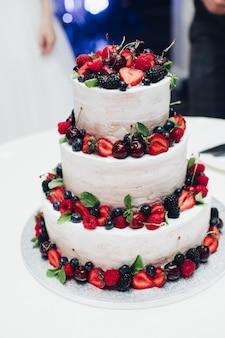 Torta nuziale a tre strati con frutti di bosco freschi, decorata con fragole, mirtilli, ciliegie e more.