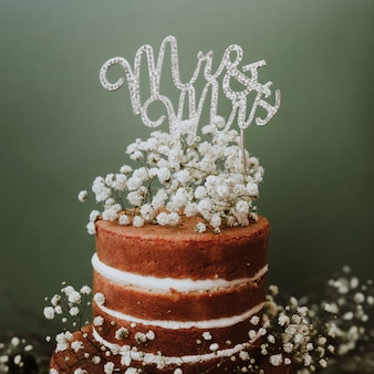 Torta nuziale con decorazione paniculata e mr e mrs topper su sfondo verde
