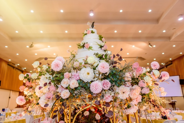 Torta nuziale decorata con fiori e candelabro alla cerimonia di matrimonio
