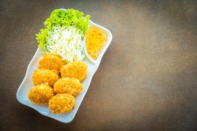 Torta o palla del gamberetto fritta nel grasso bollente con la verdura