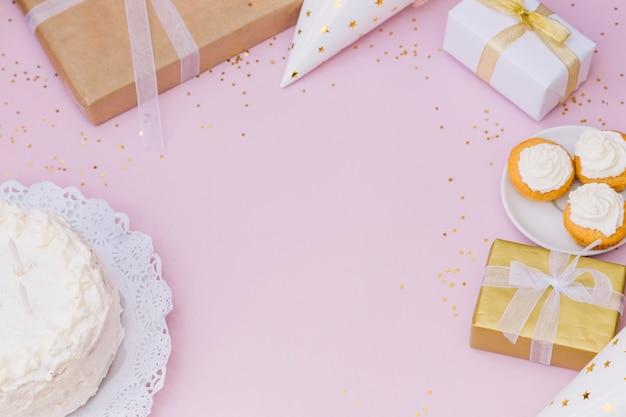 Torta; pacco regalo; regali; confezione regalo e coriandoli su sfondo rosa