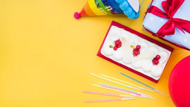 Torta rettangolare con candele; palloncino; confezione regalo e cappello di carta su sfondo giallo