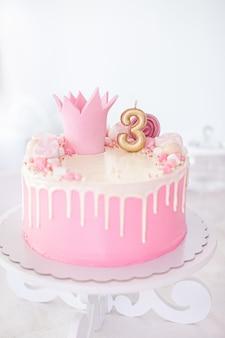 Torta rosa e bianca di buon compleanno con marshmellows e una corona e con il numero tre su uno sfondo bianco.