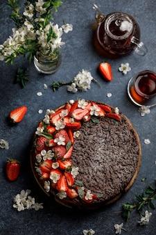 Torta rotonda al cioccolato con fragole su sfondo scuro. gustosa torta grattugiata al cioccolato