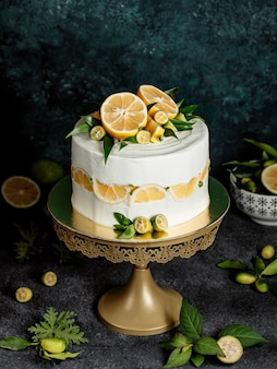 Torta rotonda decorata con crema bianca, foglie di limone e menta