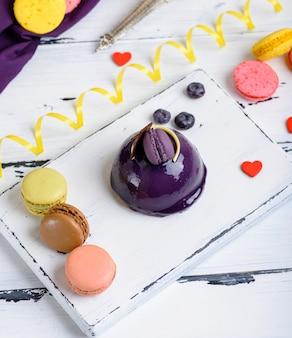 Torta rotonda lilla con macarons sul bordo di legno bianco