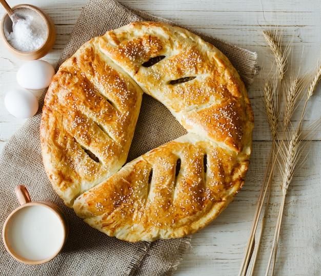 Torta rotonda su tela di sacco, uova, sale e spighe di grano e una tazza di latte, una parete di legno chiaro