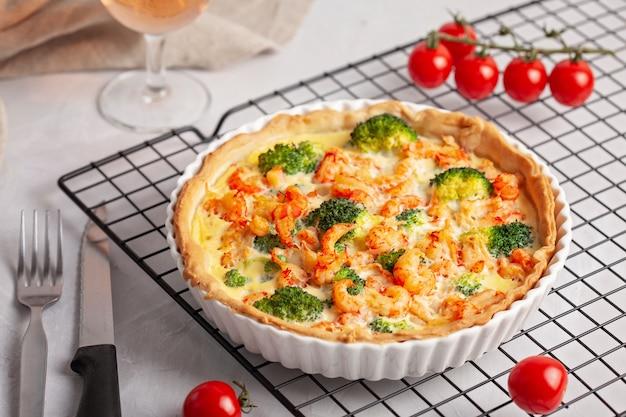 Torta salata francese fatta in casa con gamberi e broccoli ripieni di crema e uova.