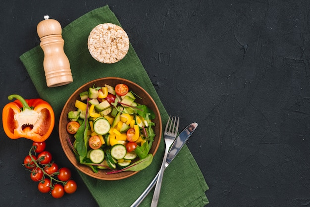 Torta soffiata di riso; insalata di verdure e pepe shaker sul tovagliolo su sfondo nero con texture di cemento