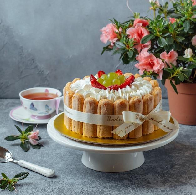 Torta tiramisù con biscotti e frutti di bosco con una tazza di tè e fiori.