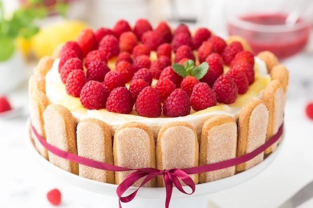 Torta tiramisù di lamponi con fiocco rosso decorato con cagliata di limone