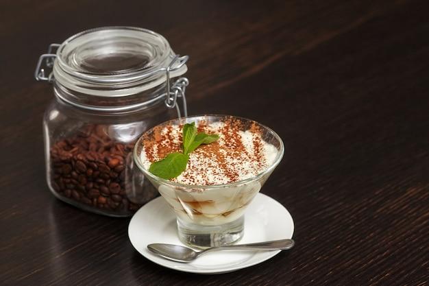 Torta tiramisù dolce in vetro con foglie di menta