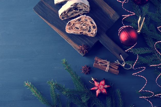 Torta tradizionale di natale con uvetta e noci con rami di albero e giocattoli