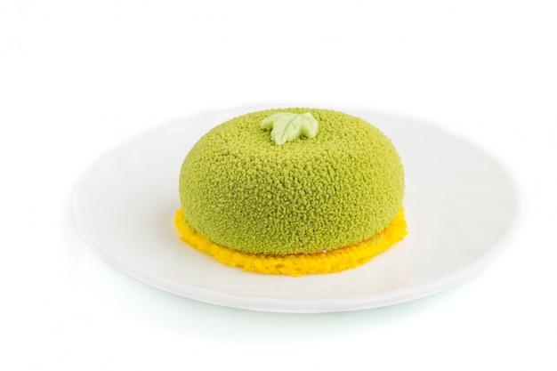 Torta verde della mousse con crema del pistacchio e della fragola isolata. vista laterale.