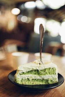 Torta verde in zolla bianca sul fondo di legno della tavola