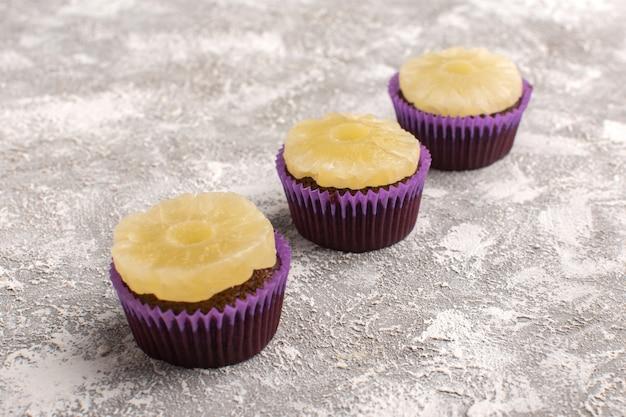 Torte al cioccolato squisite vista frontale con anelli di ananas sulla pasta dolce cuocere torta leggera scrivania