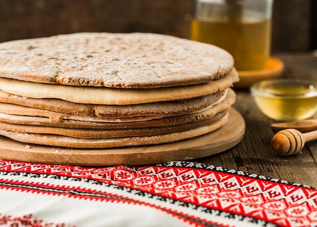 Torte al miele al forno per la torta in una pila su un tavolo di legno.