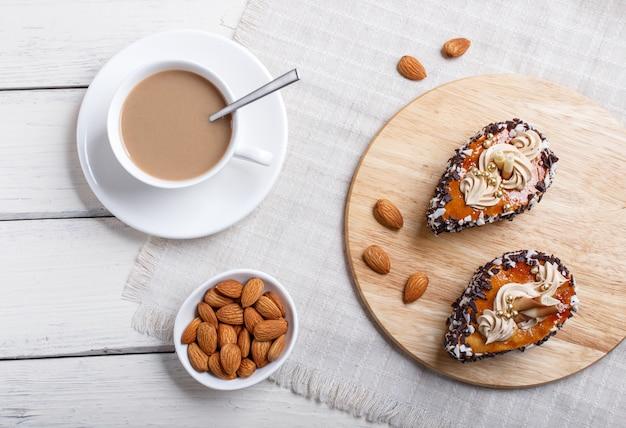 Torte con gocce di cioccolato e decorazioni color crema su legno