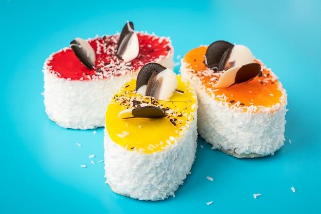 Torte con granelli, cibo malsano ad alto contenuto calorico. fiocchi di cocco su pasticceria su sfondo blu. dessert colorato al forno fatto in casa.
