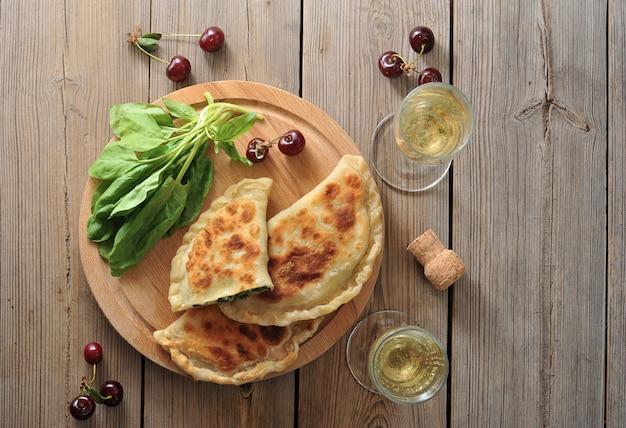 Torte con spinaci e ciliegie, bicchieri di champagne e tappo di champagne su legno