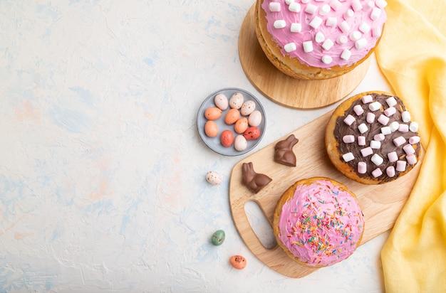 Torte di pasqua smaltate e decorate in casa con uova di cioccolato e conigli su uno sfondo di cemento bianco. vista dall'alto,