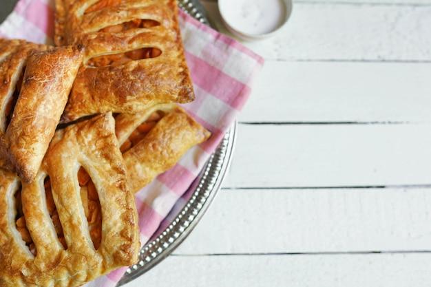 Torte e pasta sfoglia casalinghe con le mele e caramello sulla tavola di legno bianca con lo spazio della copia.