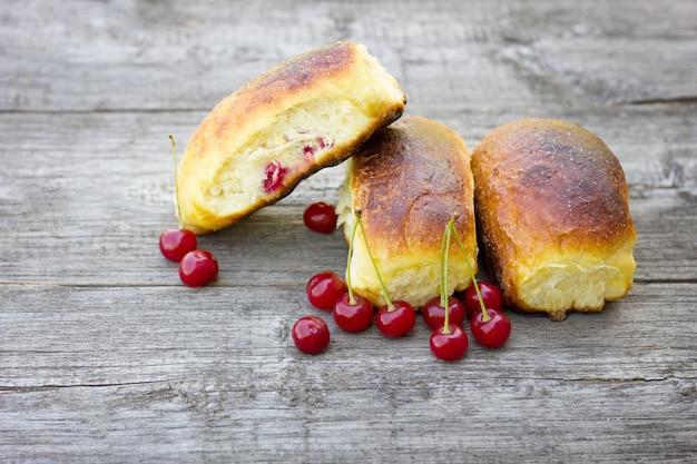 Torte fatte in casa con ciliegie su uno sfondo in legno, la composizione di prodotti naturali