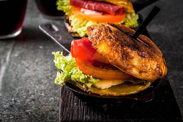 Tortilla de patatas rellena de jamon serrano in casseruola con patate, uova, sandwich con carne, lattuga, formaggio, pomodori. in padelle porzionate, con birra, tavolo in pietra nera.