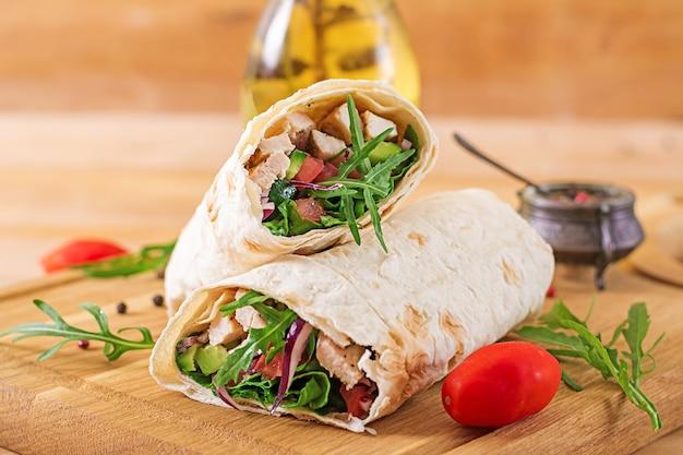 Tortillas avvolge con pollo e verdure su fondo in legno.