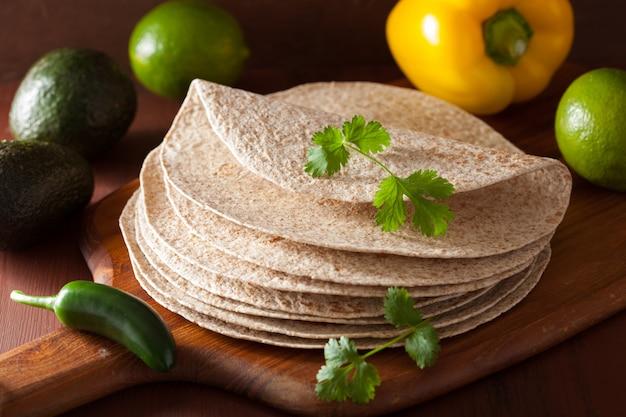 Tortillas di grano integrale su tavola di legno e verdure