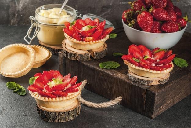 Tortine di torte fatte in casa con crema pasticcera e fragole, decorate con menta e zucchero a velo. sul tavolo di pietra nera