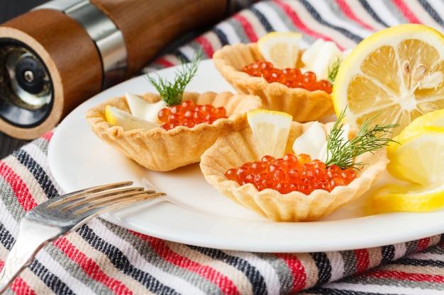 Tortini con caviale rosso su un piatto. messa a fuoco selettiva