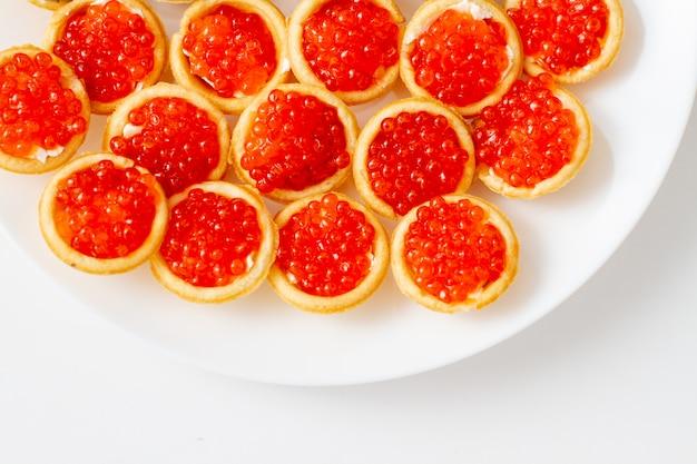 Tortini con caviale rosso sul piatto bianco