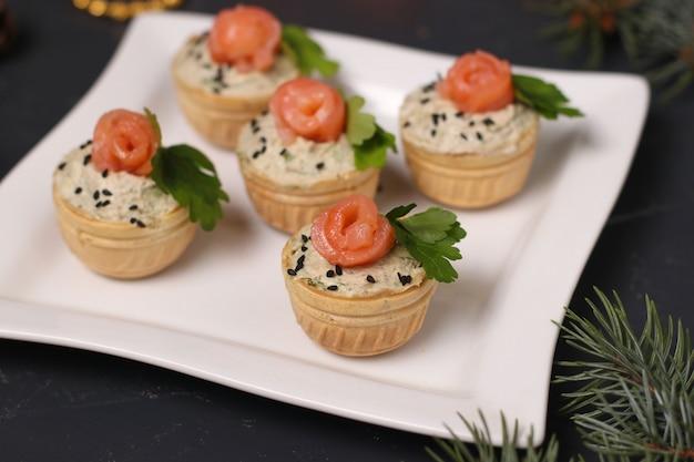 Tortini con pasta di avocado e salmone salato sul piatto bianco