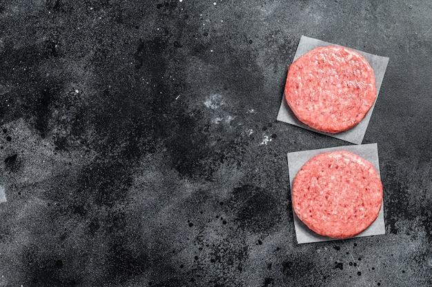 Tortini crudi dell'hamburger, carne tritata del manzo sul nero. vista dall'alto. copia spazio