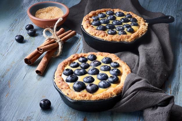 Tortini deliziosi del mirtillo con crema pasticcera alla vaniglia sulla tavola rustica leggera.
