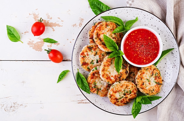 Tortini deliziosi della carne di pollo e del riso con salsa al pomodoro dell'aglio