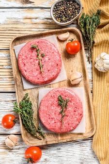 Tortini di hamburger crudo. tritare la cotoletta di carne, la carne macinata e il maiale. sfondo bianco. vista dall'alto.