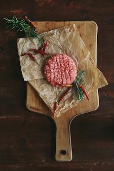 Tortini di hamburger di manzo crudo con erbe e spezie sul piatto di ardesia scuro